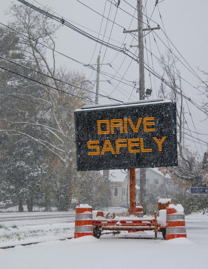Het elektrische verkeer mobiele teken door de kant van een sneeuw behandelde weg met sneeuw die die, Aandrijving veilig zegt vall stock afbeeldingen