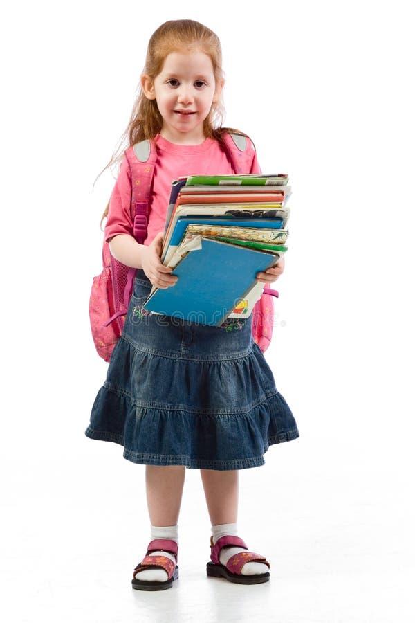 Het elementaire leeftijdsmeisje beklemtoonde door onderwijsboeken stock fotografie