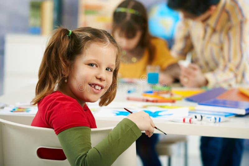 Het elementaire leeftijdsschoolmeisje schilderen royalty-vrije stock foto