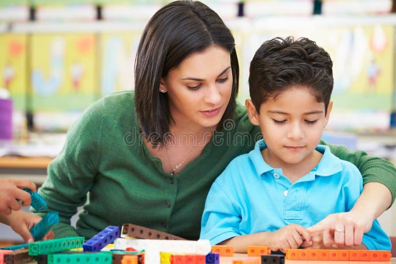 Het elementaire Leerling Tellen met Leraar In Classroom stock foto