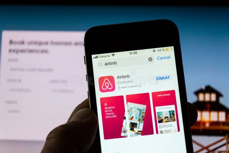 Het embleem van het Airbnbbedrijf op het scherm van de mobiele toepassingtelefoon met Internet-homepage op achtergrond royalty-vrije stock foto's