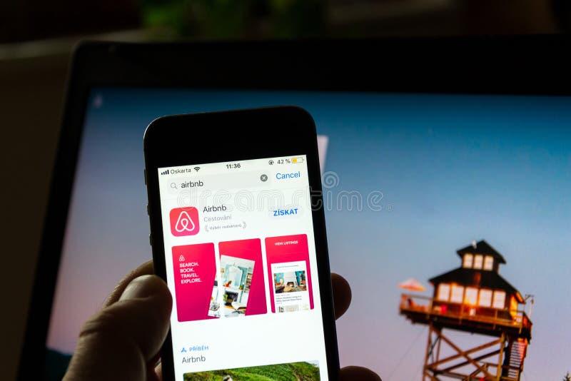 Het embleem van het Airbnbbedrijf op het scherm van de mobiele toepassingtelefoon met Internet-homepage op achtergrond stock foto