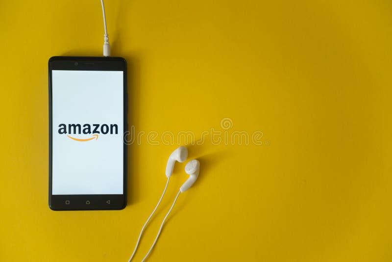 Het embleem van Amazonië op het smartphonescherm op gele achtergrond stock afbeelding