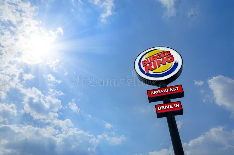 Het embleem van Burger King Restaurants tegen blauwe hemel en zon royalty-vrije stock afbeelding