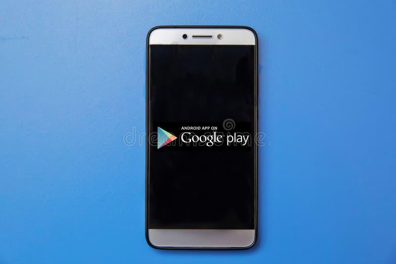 Het embleem van de het Spelopslag van Android Google op het smartphonescherm op blauwe achtergrond Smartphone van de mensenholdin stock foto