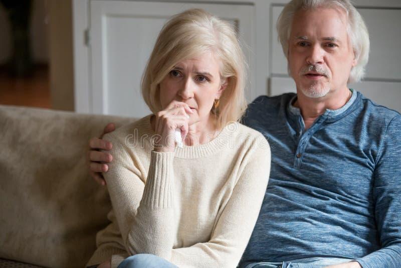 Het emotionele hogere paar wordt thuis het zenuwachtige het letten op drama van TV stock foto