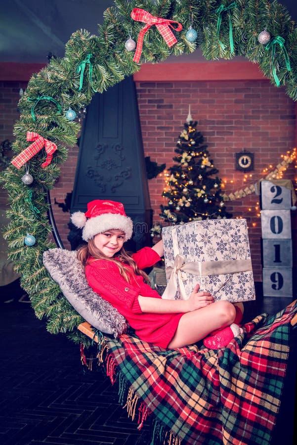 Het emotionele mooie meisje op een schommeling van de Kerstboom vertakt zich op de achtergrond van een open haard in de ruimte va royalty-vrije stock fotografie