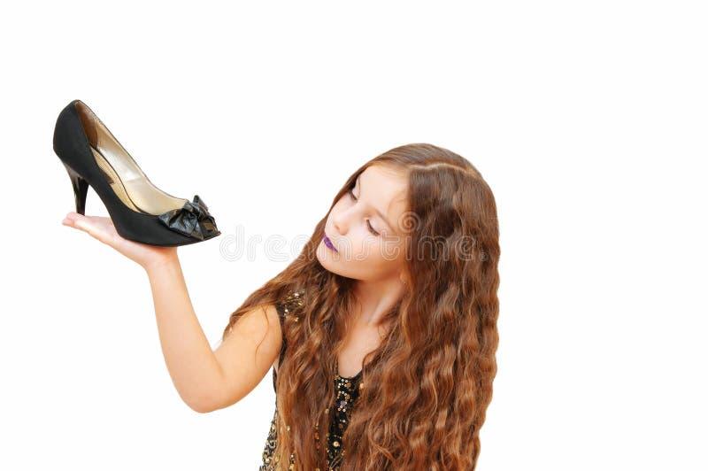 Het emotionele portret van een leuk meisje met lang haar in een kleding a houdt en probeert op high-heeled geïsoleerde schoenen, stock foto's