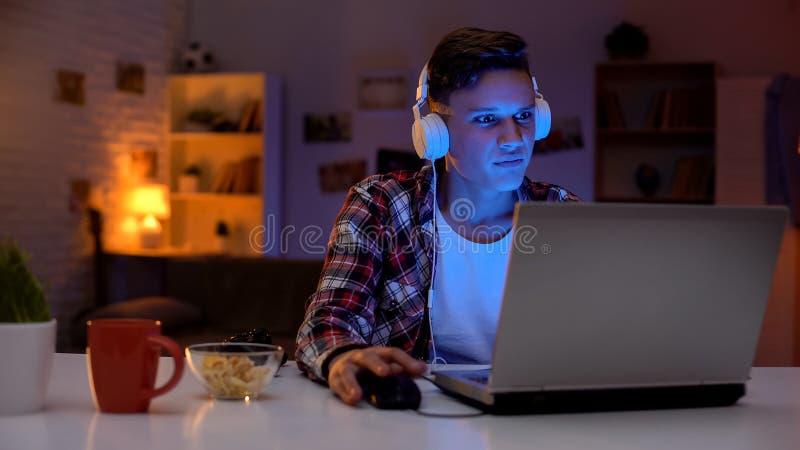 Het emotionele spel van de tiener speelcomputer op laptop en het eten van snacks, verslaving royalty-vrije stock foto