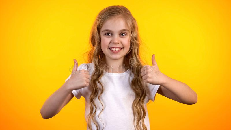 Het emotionele tienermeisje die dubbele duim-omhooggaand maken, stelde uiterst kind, promo tevreden stock foto