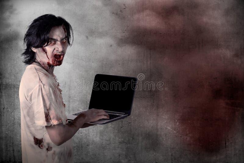 Het enge mannelijke zombie typen met laptop royalty-vrije stock afbeeldingen