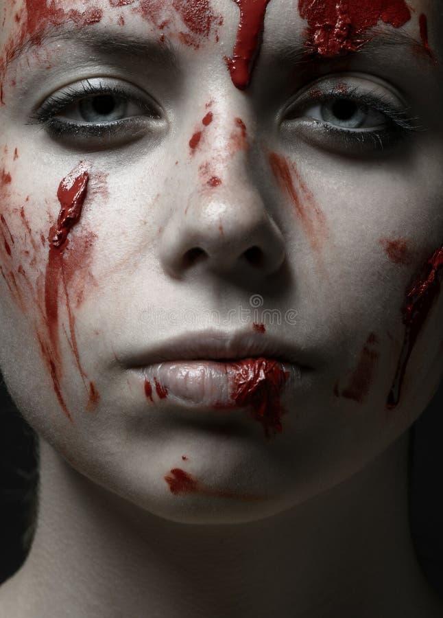 Het enge Meisje en Halloween als thema hebben: portret van een gek meisje met een bloedig gezicht in de studio stock foto
