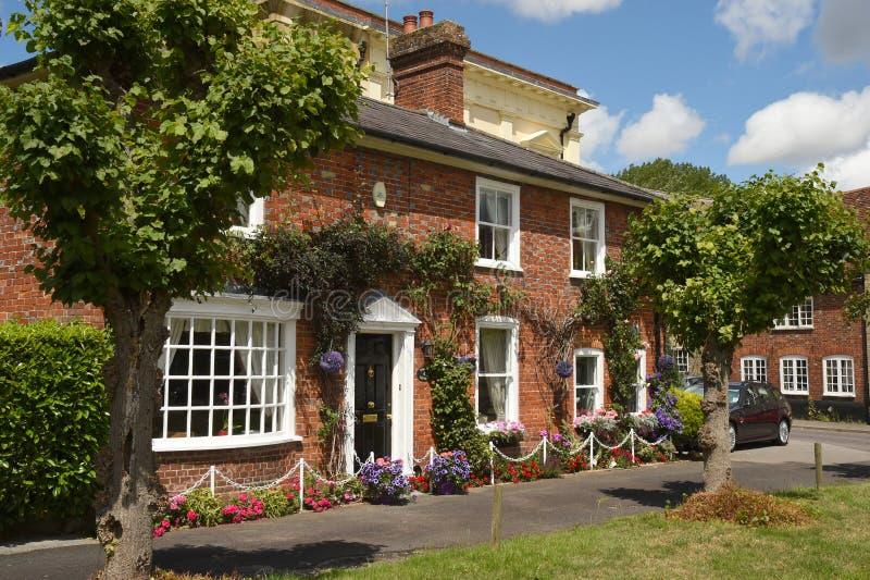 Het Engelse huis bedecked met bloemen op het groene dorp stock afbeelding