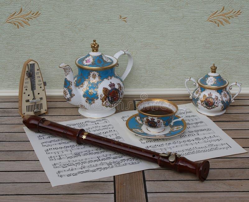 Het Engelse theekopje met schotel, de theepot en de suiker werpen, metronoom voor muziek en een blokfluit op een blad van muziek royalty-vrije stock foto's