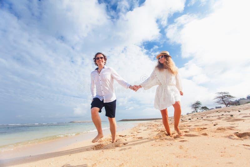 Het enkel gehuwde huwelijkspaar houdt handen en het lopen bij strand stock afbeeldingen
