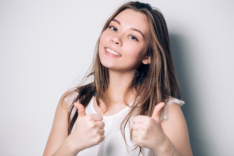 Het enthousiaste gemotiveerde aantrekkelijke jonge vrouw geven duimen omhoog stock afbeeldingen