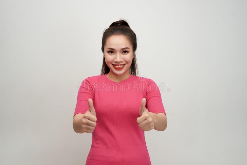 Het enthousiaste gemotiveerde aantrekkelijke jonge vrouw geven duimen op gebaar van goedkeuring en succes met een richtende gliml royalty-vrije stock foto