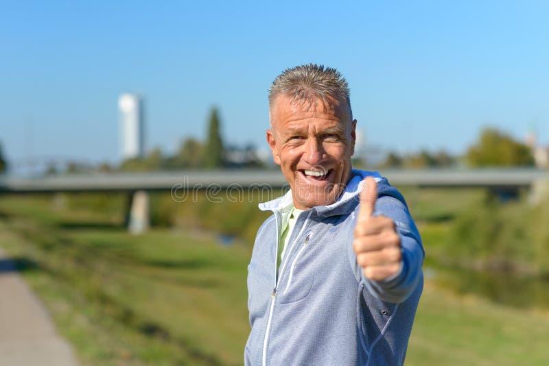 Het enthousiaste gemotiveerde mens geven duimen omhoog stock fotografie
