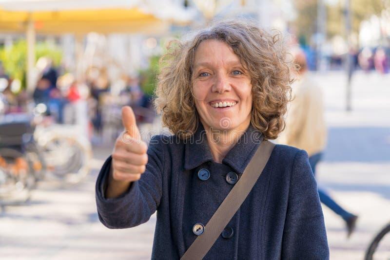 Het enthousiaste gemotiveerde vrouw geven duimen omhoog stock foto