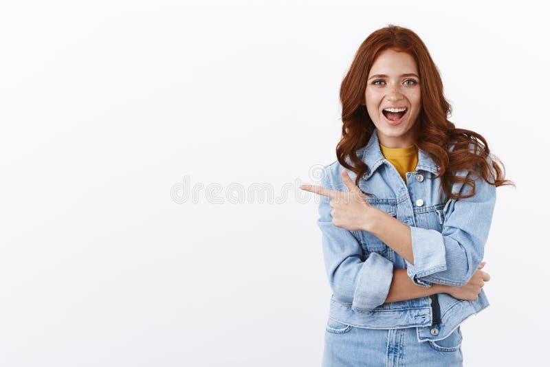 Het enthousiaste sassy knappe gember meisje met freckles in het denim jack dat naar links wijst, glimlachend en geamuseerd royalty-vrije stock afbeelding