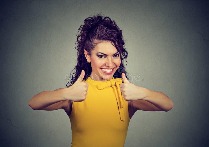 Het enthousiaste vrouw geven beduimelt omhoog gebaar van goedkeuring en succes stock fotografie