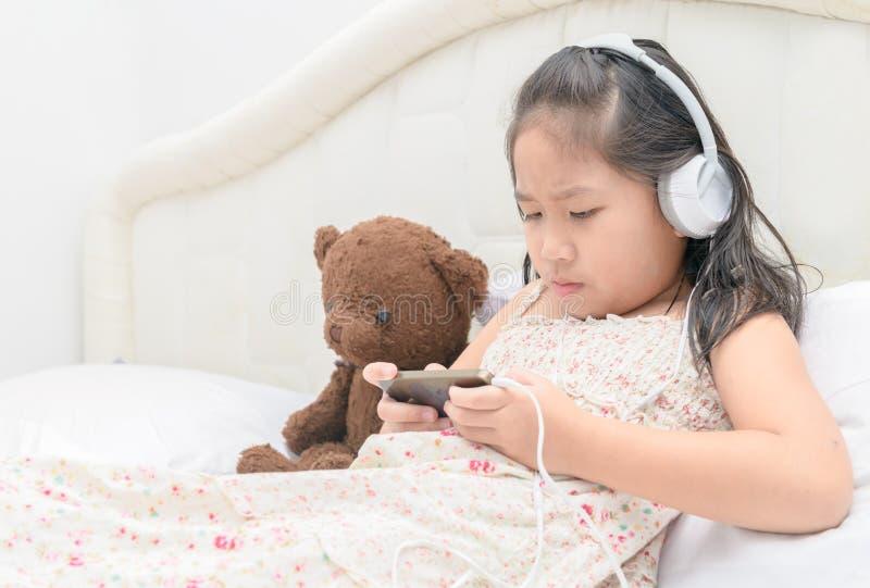 Het ernstige Aziatische meisje spelen op smartphone stock afbeeldingen