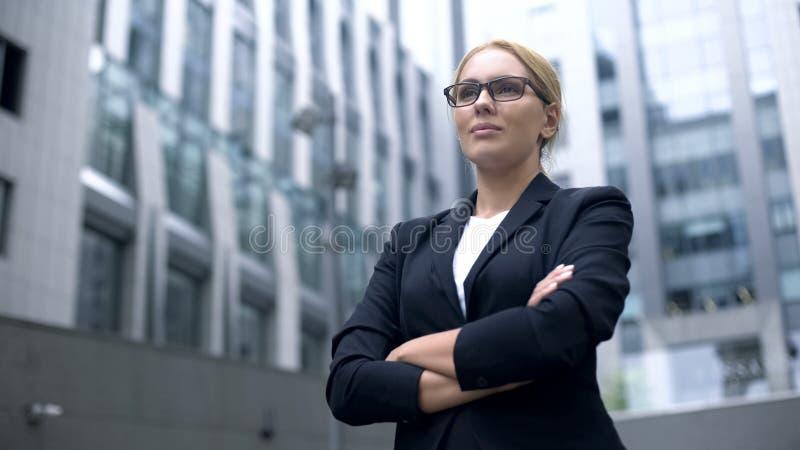 Het ernstige bedrijfs gekruiste dame glimlachen, wapens, professionalisme en ervaring royalty-vrije stock foto's