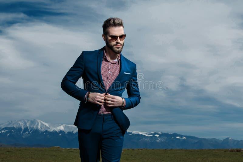 Het ernstige kijken mens die zijn jasje aanpassen en het lopen royalty-vrije stock afbeeldingen