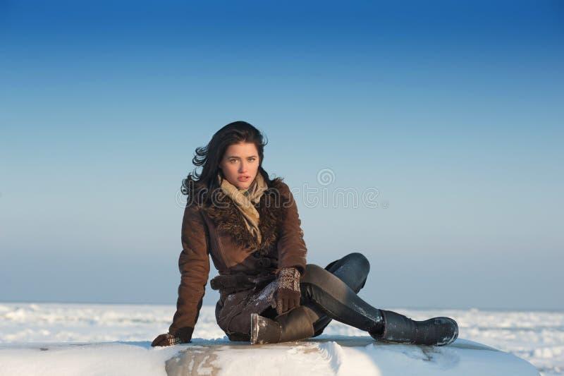 Het ernstige meisje stellen op de sneeuw stock afbeeldingen