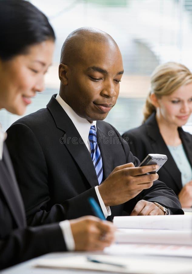 Het ernstige overseinen van de zakenmantekst op celtelefoon stock foto's
