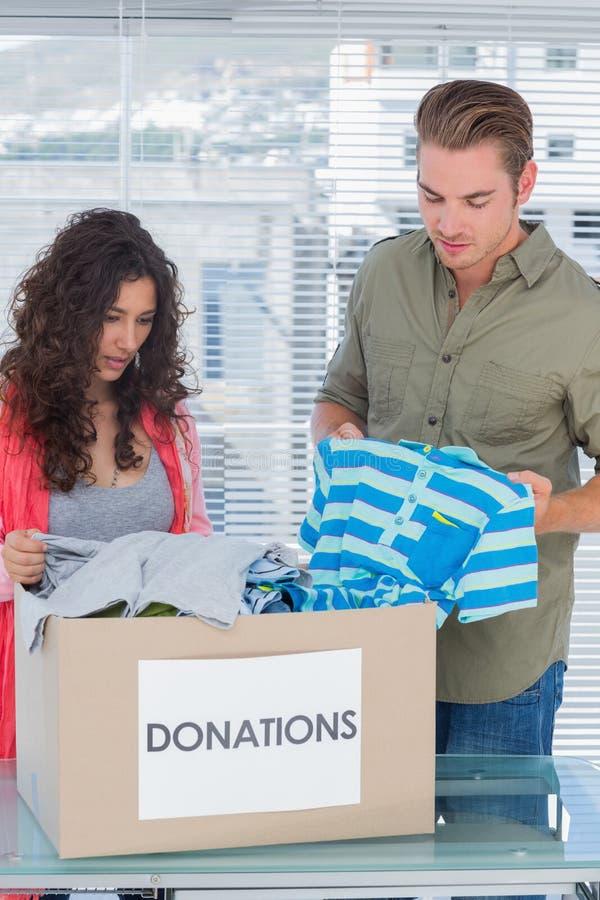 Het ernstige vrijwilligers nemen kleedt zich van een schenkingsdoos stock afbeeldingen