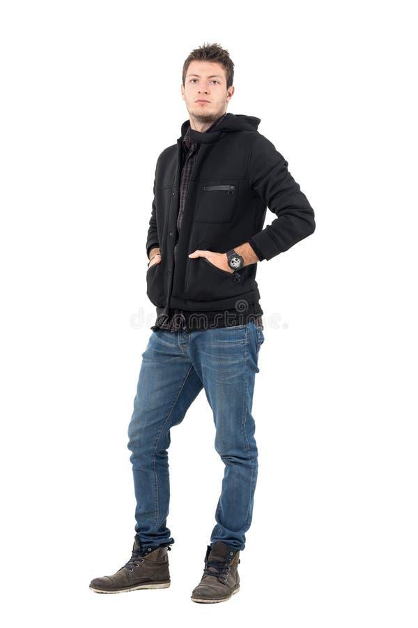 Het ernstige zekere mannelijke model in zwart jasje met een kap met dient zakken in stock fotografie