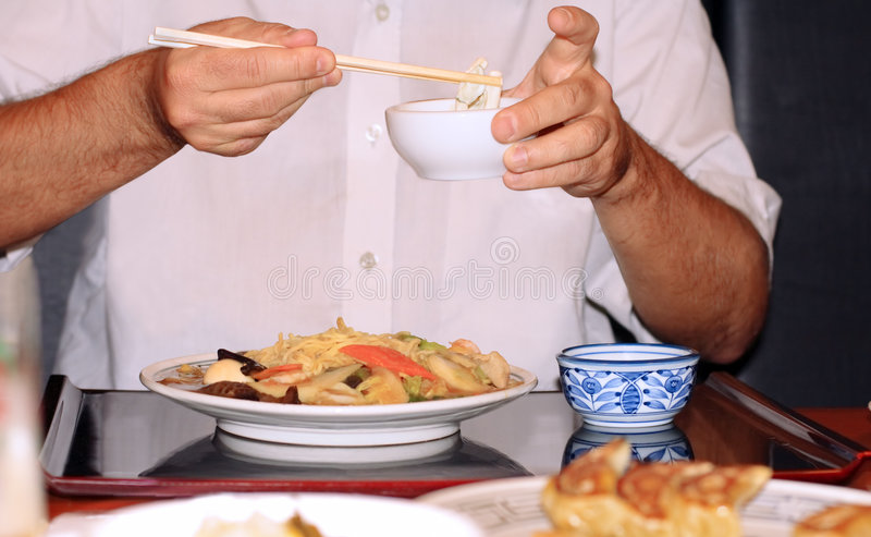 Het eten met eetstokjes stock afbeelding