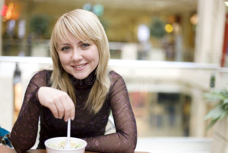 Het eten van blond meisje met lepel in restaurant stock afbeeldingen