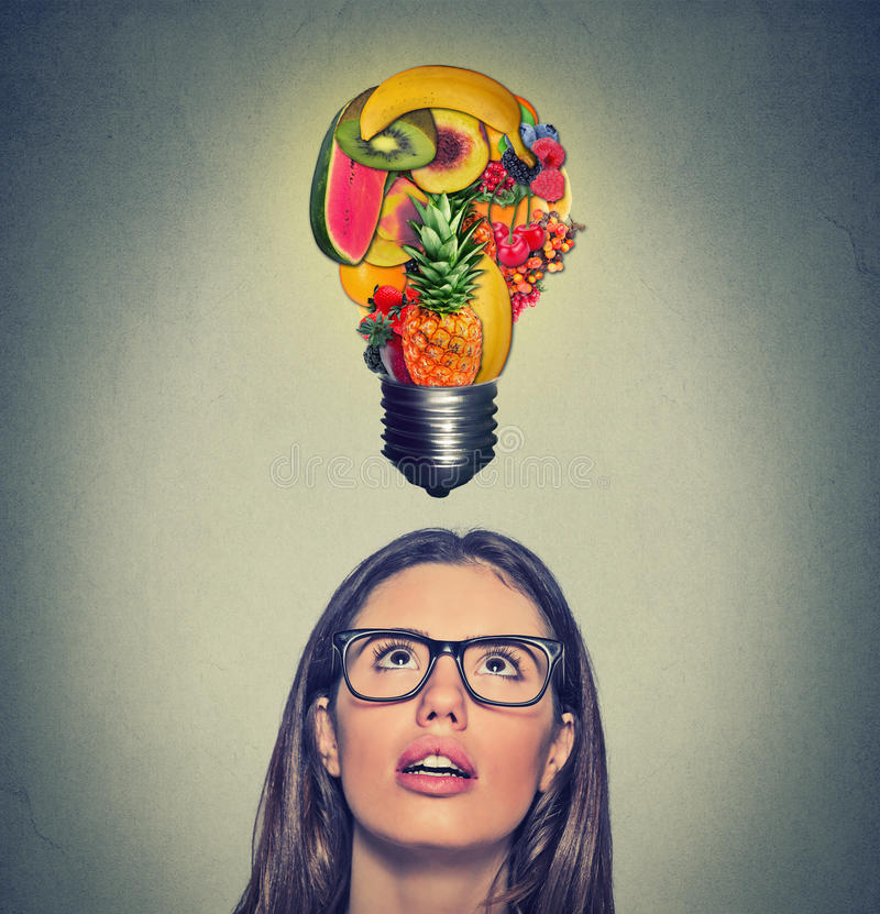 Het eten van de gezonde uiteinden van het ideedieet vrouw die omhoog gloeilamp kijken die van vruchten boven hoofd wordt gemaakt royalty-vrije stock afbeelding
