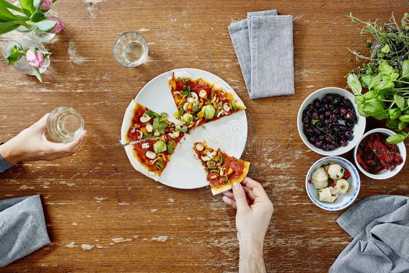 Het eten van en het delen van organische pizza bij dinerpartij royalty-vrije stock afbeelding