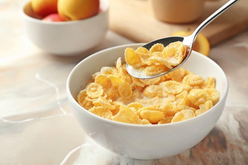 Het eten van gezonde cornflakes met melk van kom op lijst, close-up stock foto