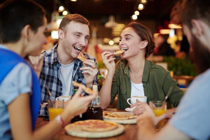 Het eten van Heerlijke Pizza met Vrienden stock foto