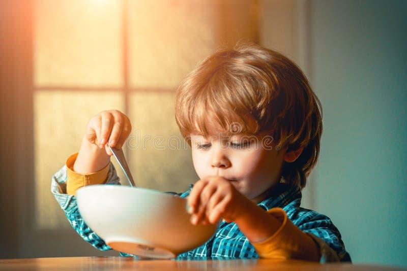 Het eten van het jonge geitje Weinig jongen die ontbijt in de keuken hebben Leuk kind die ontbijt thuis eten Baby het eten royalty-vrije stock afbeelding