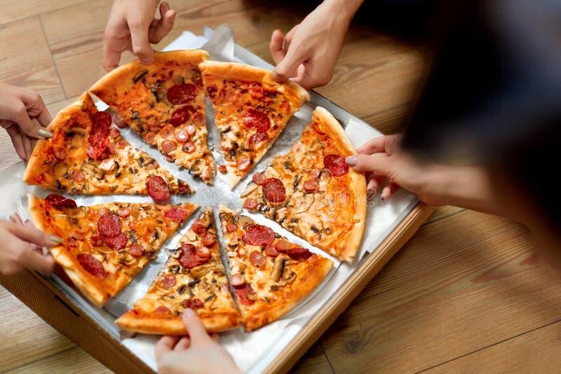 Het eten van Pizza Groep Vrienden die Pizza delen Snel Voedsel, Vrije tijd royalty-vrije stock afbeelding