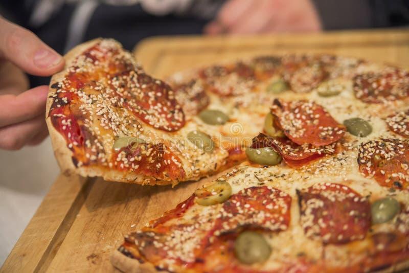 Het eten van voedsel Close-up van Mensenhanden die Plakken van Pepperonis nemen royalty-vrije stock foto's