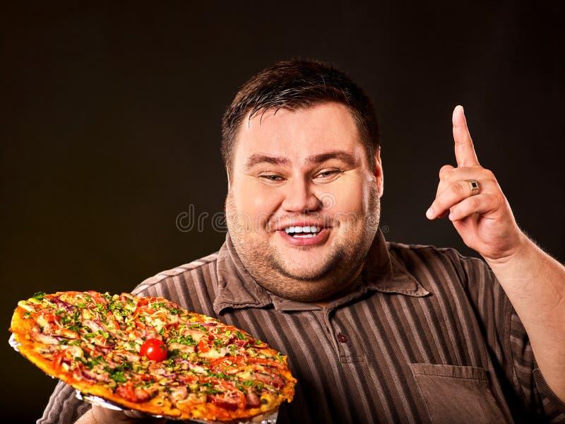 Het eten van wedstrijdpizza Vette mens die snel voedsel voor te zware persoon eten stock foto's