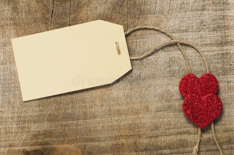 Het etiket van het document met kabel en rode harten stock foto