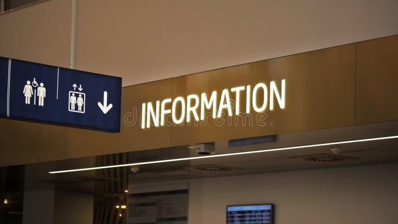 ` Het etiket van het informatie` neon over infopointbureau, en hangend toiletten en liftenpictogram bij luchthavenzaal royalty-vrije stock fotografie