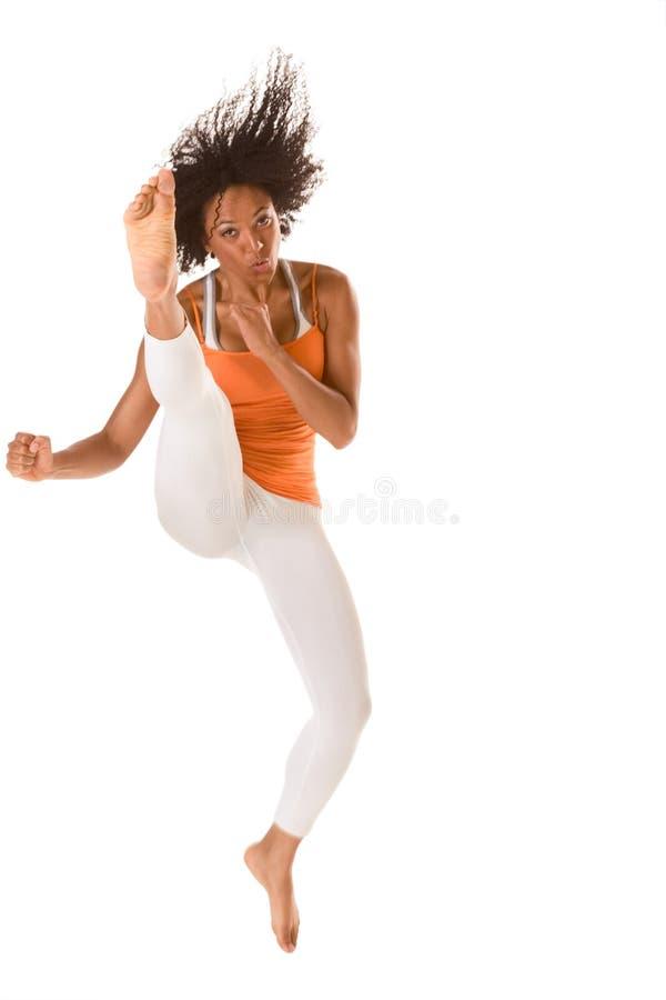 Het etnische geschiktheidsvrouw springende schoppen (motieonduidelijk beeld stock fotografie