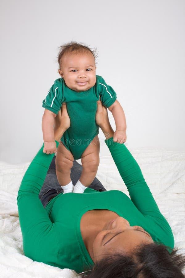 Het etnische moeder spelen met haar zoon van de babyjongen op bed royalty-vrije stock afbeelding