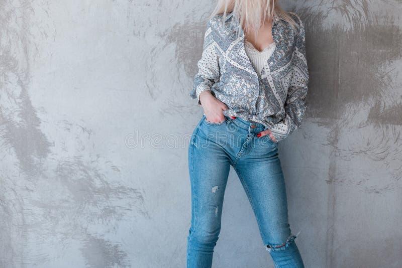 Het Europese jonge vrouw model stellen dichtbij een grijze muur in modieuze de jeugdkleren De zomerinzameling van de kleding van  stock fotografie