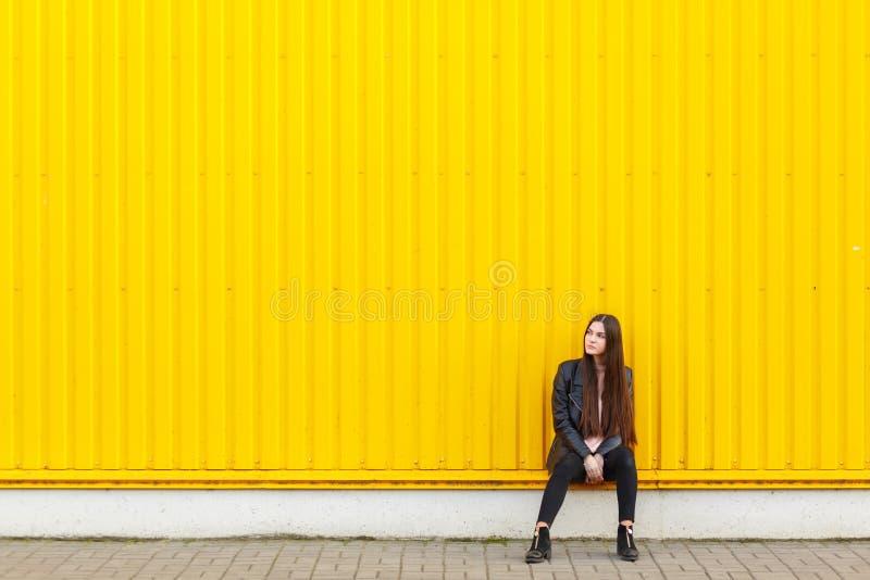 Het Europese meisje in een leerjasje, zit dichtbij een muur en kijkt aan de kant stock foto's