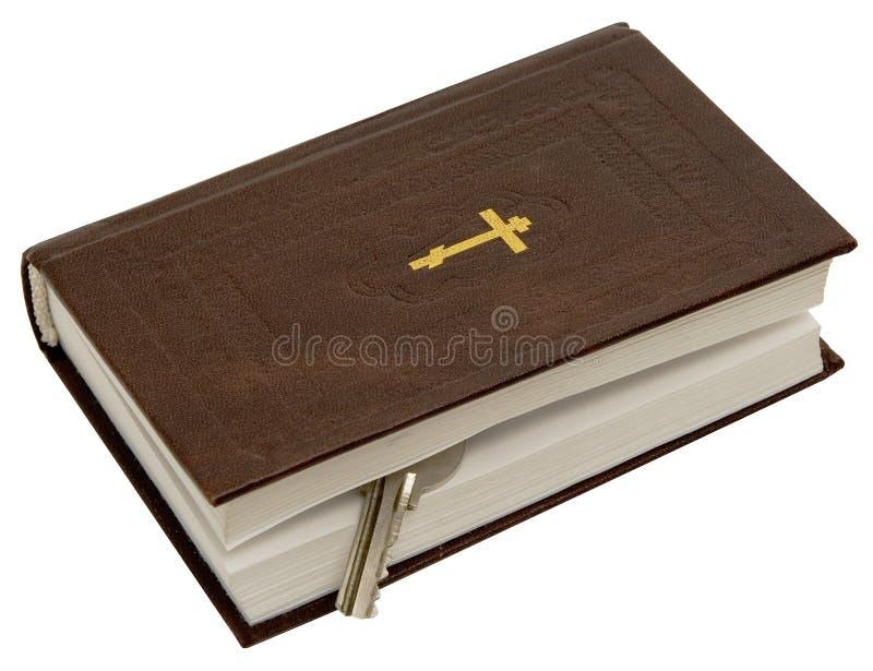 Het evangelie met een sleutel op een witte achtergrond. Foto royalty-vrije stock afbeelding