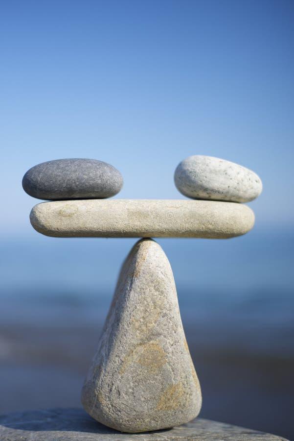 Het in evenwicht brengen van zwart-witte kiezelstenen op de bovenkant van steen stock foto's